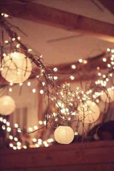 Hang rustic garland from the ceiling for soft lighting for your wedding reception. #RusticWedding #WeddingDecor