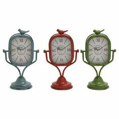 """Add a touch of retro-inspired style to your nightstand or desk with this weathered metal table clock, showcasing a bird finial and Roman numerals.   Product: Set of 3 table clocksConstruction Material: MetalColor: Light blue, red, and greenFeatures: Sparrow accentAccommodates: (1) AA Battery - not includedDimensions: 15"""" H x 9"""" W x 6"""" D"""