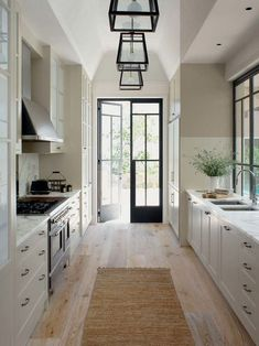 Design ideas for a traditional galley kitchen in Central Coast with a double-bowl sink, shaker cabinets, white cabinets, marble countertops, white backsplash, paneled appliances and light hardwood floors. — Houzz #MinimalistHomeAppliances