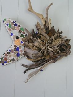A fish for the wall made from driftwood and colored rocks and shells....totally beachy!