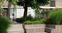 Rodenburg tuinen: achtertuin met hoogteverschil, inclusief een decoratief element in de vorm van een spiegelvijver. Het hoogteverschil is afgewerkt door traptreden te maken van hardhout. Hierbij is er ook een extra zitplek in de tuin ontstaan.