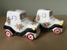 This is a sweet unique pair of model T style porcelain ceramic cars as salt and pepper shakers made in post war Japan. The charming shakers are decorated with pink painted flowers. They are porcelain and stand 2 inches tall and 3 inches long. The hole corks are missing. They are marked Japan on the bottom. This set is in excellent condition.