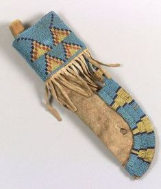 Northern Plains Beaded Hide Knife Case, Blackfeet, c. last quarter 19th century, sinew sewn buffalo hide form beaded on one side with multicolored stepped triangle elements on a light blue ground, the lower end partially stitched with metal wire, includes an old antler-handled knife, (minor bead loss), lg. 12 1/2 in. Estimate $5,000-7,000