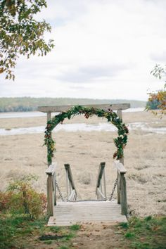 Pretty floral arch at a lakefront ceremony.   Photography: Emily Delamater Photography - www.emilydelamaterphotography.com