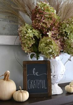 Thanksgiving decorations - simple mantle scape with hydrangeas and white pumpkins.