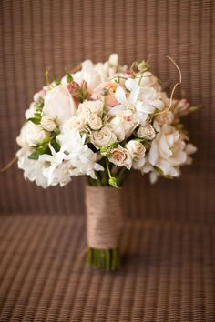 A few pieces of curly willow tips in this bouquet of roses, ranunculus, snap dragons and orchids make it look rustic and elegant.