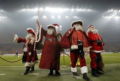 People wearing Santa Claus costumes stand on the field before the start of the Italian Serie A soccer match between AC Milan and Cheivo at the San Siro Stadium in Milan