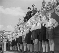 Communist Era--Young Pioneers in East Germany attend a political rally in 1951, displaying their unique bent-elbow hand salute, designed to contrast with the former straight-armed Hitler salute.