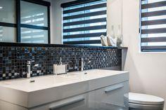 Projet de salle de bain contemporain : tout en contrastes en noir et blanc, stores alternés, céramique lappato, céramique grands et petits formats, vanité laquée blanche. Le miroir apporte un effet de grandeur à la pièce.