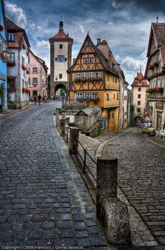 No, it's not always sunny in Rothenburg, Germany. This view shows a special intersection with the 'Silberturm' (White Tower) gateway in the background and the road heading down to the river. The ochre building still retains the fish tanks used to sell the catch.