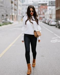 A ruffled sweater with slim jeans, a crossbody bag, and suede boots.