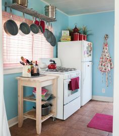 hang pots and pans to save space.  with white appliances and cabinets, the robins egg blue walls are very pretty