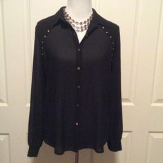 Listing Sheer Flowy Black Blouse This beautiful blouse is slightly sheer with an understated stud detail at the shoulders and lovely gold buttons down the front. The loose drapey silhouette really flatters the shape. It's longer in the back and looks great loosely tucked into a favorite pair of jeans or slacks. Excellent condition. Size small but fits loosely. Chloe K Tops Button Down Shirts