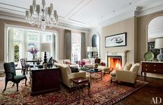 In the living room of a Manhattan townhouse renovated by Brian Sawyer and John Berson, neoclassical French mirrors from H. M. Luther flank a Picasso ink drawing and a Sawyer|Berson-designed mantel made by Chesney's. The bespoke sofa and club chairs, all upholstered in a Larsen silk, are grouped atop an antique Herati carpet, and a Holland & Sherry velvet covers the walls.