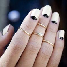 Half moon, reverse french manicure. Nude and black nail polish. The midi gold rings totally complete the look. Love these nails!