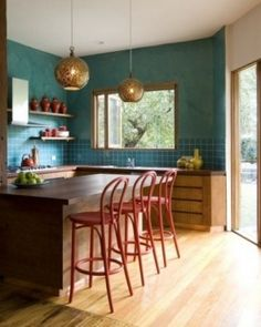 Vibrant aqua paired with red, dark wood and hammered pendant lights makes a bold statement in this Port Melbourne kitchen designed by Camilla Molders. The large windows let in a flood of light from the gardens and beckon you to carry your meal outdoors.
