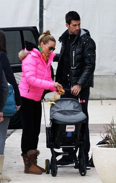 Happy family: Novak Djokovic and his wife Jelena looked the picture of a happy family as they were seen taking a short walk with their baby son, Stefan, and their pet dogs in Belgrade on Sunday