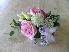 Pretty wedding wrist corsage in pink and lilac with freesia and astrantia.  Flowers by Honey Pot Flowers.  Venue The Tythe Barn, Bicester