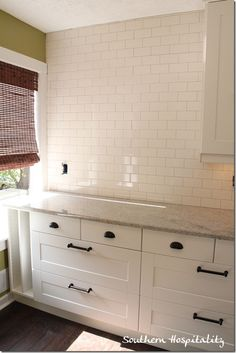 Granite, White cabinets with oil rubbed bronze hardware and white subway tile with gray grout.