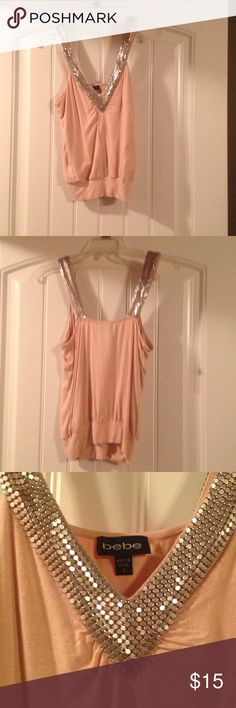 Bebe peach metal tank size small Like new size small v-neck peach colored Bebe tank bought at retail store in Las Vegas. Elastic band at bottom of shirt and metal detailing along straps on front and back. No missing pieces. 93% rayon; 7% spandex. Hand wash cold. Non- smoking home always. bebe Tops Tank Tops