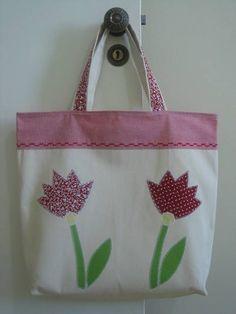 Linda bolsa feita em algodão cru super resistente com aplicação de tulipas em ponto caseado. Perfeita para qualquer ocasião!  **Medida não inclui a alça** **Preço promocional válido somente para essa bolsa a pronta entrega** R$ 27,00