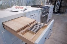 Knife drawer and hidden chopping board Wellborn Cabinets- Finish: Back Wall - Maple Glacier; Island - Willow Door Style: Messina Countertops: Caesarstone Fresh Concrete; Calcutta Latte Floor Tile: Logwood Grey Grout: Mapei Pewter Photo by: Dennis McDaniel