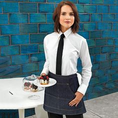 An alternative way to style our new black denim cropped apron. Dressed up or down, this is a style staple for your workforce # PremierWorkwear Bartender Uniform, Waiter Uniform, White Shirt Black Tie, Black Denim, Black Pants, Waitress Outfit, Cafe Apron, Hotel Uniform, Work Clothes