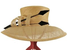 A striking design of a hat, with your eye drawn instantly to the three arrow shaped feathers that are secured to the crown by a twist of sinamay material which matches the brim. The crown is a medium straw weave and the brim bows delicately downwards towards the face.