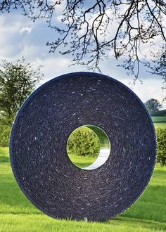 The Slate and Steel Torus is a variation on the subtle convex curves and central portal of the original sculpture.