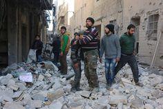 Ein Syrer tröstet einen Jungen nach Luftangriffen auf den Stadtteil Al-Kalasa...