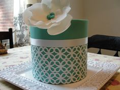 Teal Cake - The design was made by punching edible paper with a craft punch, the ribbon is real, and the flower is gumpaste.  The cake is a 6-inch cake, just under 7 inches tall.  This design is inspired by Jessica Harris' second Craftsy class.