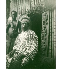 Bamileke Basoa fon with his attendant holding a prestige KI SMOKING PIPE and a horse-tail beaded fly-whisk. (1920)  Photographer: Frank H. Christol Source: PITT RIVERS MUSEUM, UNIVERSIT