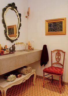 O piso de ladrilho hidráulico da Dalle Piagge dá um ar vintage ao banheiro. A pia de concreto moldado tem metais dourados. Espelho comprado no Lar Escola São Francisco. O quadro emoldura um lenço adquirido em Brasília, na A Referência Galeria de Arte. Mesa da Casa Velha.