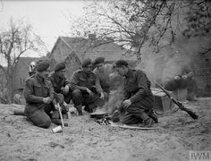 Royal Marines of the 45th Royal Marine Commandos cook up a meal at Drevenack,Germany. 28 March 1945.