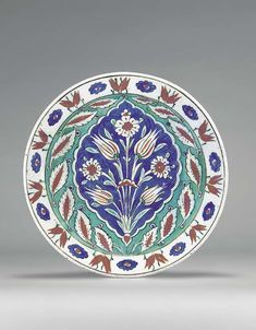 AN IZNIK POTTERY DISH OTTOMAN TURKEY, CIRCA 1580 With sloping rim on short foot, interior with a central cusped blue ground cartouche containing a symmetrical arrangement of two pairs of red & white striped tulips alternating with red & white flowerheads, all springing from central tuft, cavetto with white & red saz leaves on green ground, white rim with paired red tulips & simple blue flowerheads, exterior with alternating blue paired tulips & green roundels, 12in. (30.6cm.) diam.