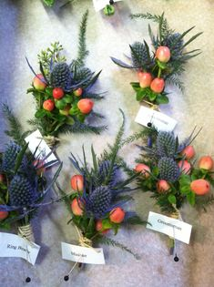 Blue eryngium boutonnieres with coral hypericum berries and plumosa foliage.