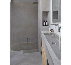 Com exceção das prateleiras de madeira, o cimento queimado reveste todo este banheiro