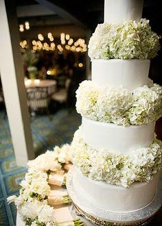 Pastel de cuatro pisos con adornos de flores naturales.