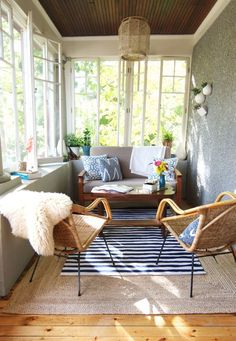 A striped outdoor rug above a textured jute rug creates an earthy, yet contemporary look in this enclosed porch.