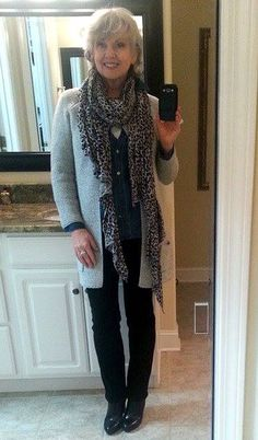 Wearing a light gray sweater coat over a denim shirt and a white tank with black jeans and boots and long black and gray knit animal scarf.