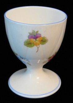 This is an eggcup or egg cup made by Shelley China, England in the Rose Pansy and Forget Me Not pattern 13424 and the Dainty shape with blue trim made 1940-1966