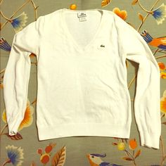 Lacoste White Long Sleeved V Neck Classic Lacoste white long sleeved v neck long sleeved top. Size 36 suits like medium. Gently used with a small spot shown in the third picture. Lacoste Tops