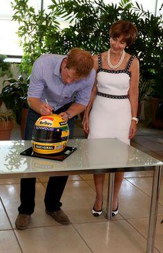 Prince Harry signs a replica Ayrton Senna helmet accompanied by Ayrton Senna's sister, Vivienne Senna, at the Ayrton Senna Institue on June 26, 2014 in Sao Paulo Brazil.