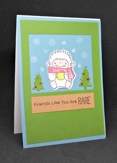 A yeti is enjoying a warm beverage sitting between two trees with enamel decorations on an area of blue with snowflakes falling. There is a frame of green with a box that has the following stamped in black 'Friends like you are rare', with a blue border around everything.