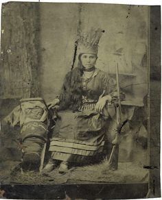 "Full Plate Tintype of ""Prairie Flower"" Indian Trick Shooter, a  lovely young mother in full Iroquoian dress with full feathered bonnet seated with her child on cradle board to left and her rifle to her right."