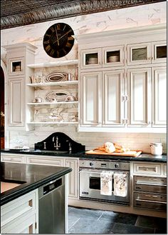 oh my! marble tile to the tin ceiling, dark quartz, granite or soapstone countertops on white painted cabinets, dark stone floor