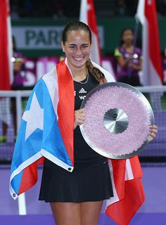 Monica Puig of Puerto Rico holds the winners trophy and her national...