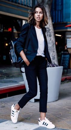 Casual style from 30 ways to wear sneakers to work—slim trousers (tailored to perfection) with a white tee or silk blouse + a dark royal blue tight stretch blazer, and Adidas black 3 stripe Rock Star tennis shoes.