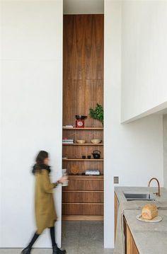 034 DSC3864. El propio estudio ha diseñado el mobiliario de cocina. Los armarios se han fabricado con madera de nogal, mientras que en la encimera se ha colocado la misma piedra italiana que reviste los suelos. La grifería de color dorado es de Vola. Electrodomésticos, de Míele y Siemens. Boles de madera, de HK.