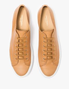 Athletic-inspired low top leather sneaker from Common Projects in Tan.  Features round toe, lace up front, metal eyelets, flat cotton laces, leather uppers, leather lining, suede heel, matching thread and white rubber outsole.  •	Low top leather sneaker